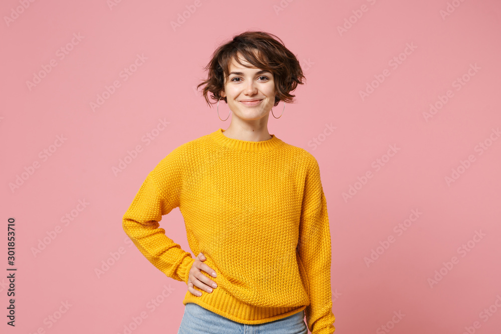 Fototapety, obrazy: Smiling young brunette woman girl in yellow sweater posing isolated on pastel pink wall background, studio portrait. People sincere emotions lifestyle concept. Mock up copy space. Looking camera.