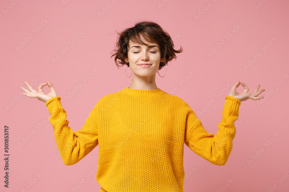 Fototapeta Young brunette woman girl in yellow sweater posing isolated on pastel pink background. People lifestyle concept. Mock up copy space. Hold hands in yoga gesture relaxing meditating keeping eyes closed.