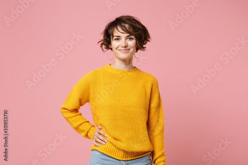 Pinturas sobre lienzo  Smiling young brunette woman girl in yellow sweater posing isolated on pastel pink wall background, studio portrait