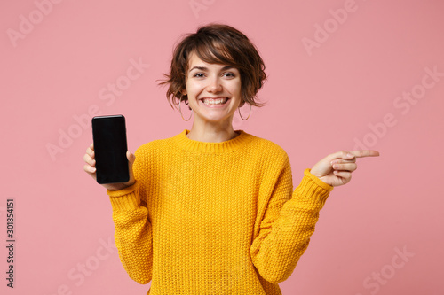 Foto  Smiling young woman girl in yellow sweater posing isolated on pastel pink background