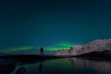 Man Watching The Northern Lights, Aurora Borealis, Devil Teeth Mountains In The Background, Tungeneset, Senja, Norway