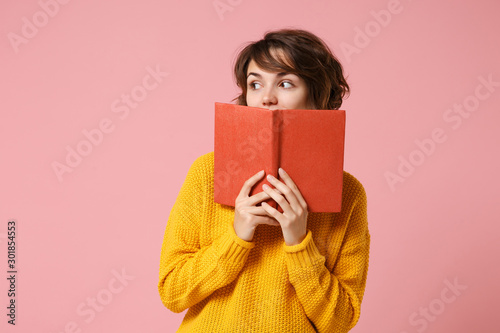 Fotografía  Young brunette woman girl in yellow sweater posing isolated on pink wall background studio portrait