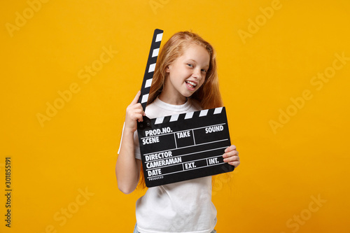 Fényképezés Cheerful little ginger kid girl 12-13 years old in white t-shirt isolated on yellow background in studio