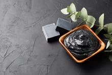 Spa And Bath Concept. Dead Sea Mud, Coal Black Soap, Eucalyptus On Black Background. Copy Space.