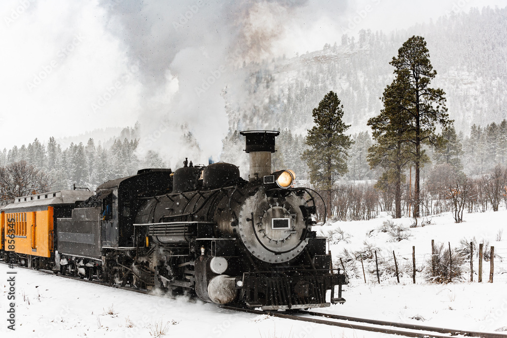 Fototapety, obrazy: Vintage Steam Train Billowing Smoke in the Snow as it Moves Through the Mountains.