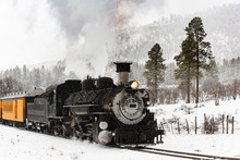 Vintage Steam Train Billowing Smoke In The Snow As It Moves Through The Mountains.