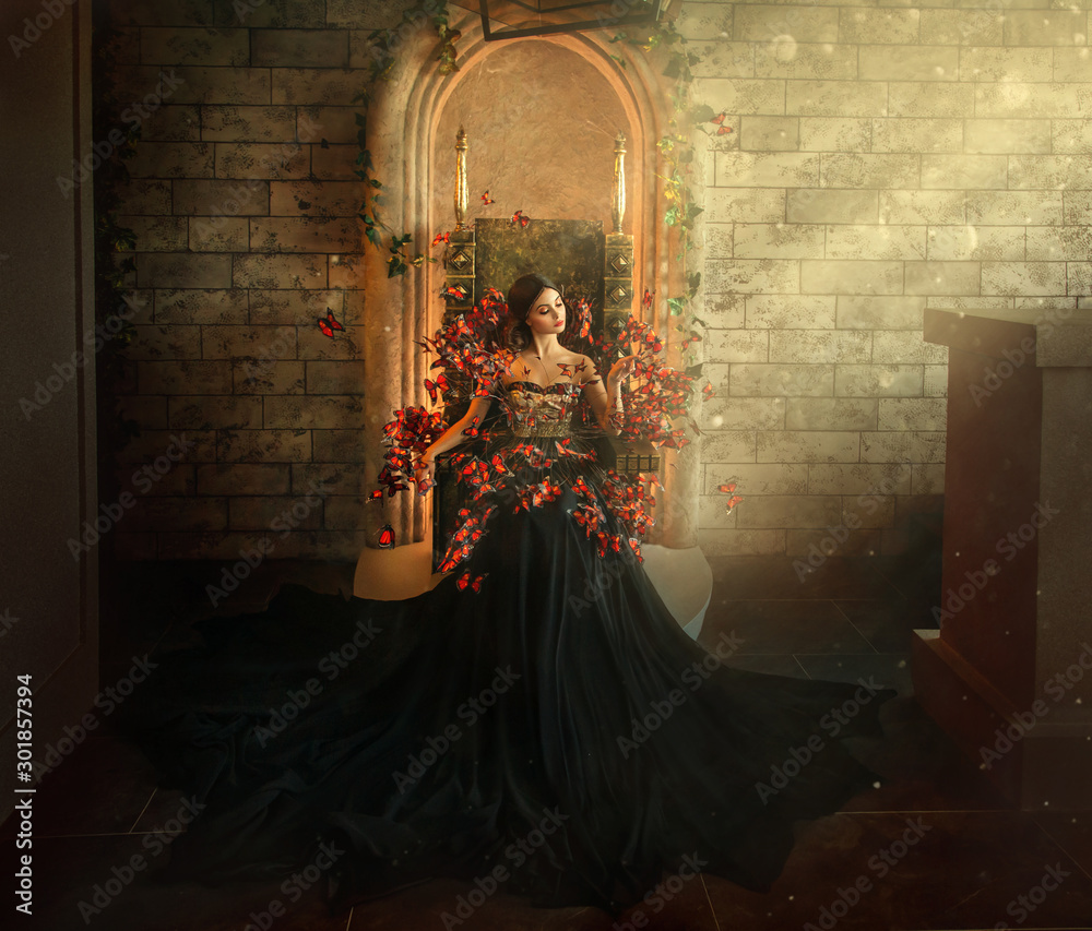 Fototapeta gothic dark queen sits in castle on golden throne. black dress with butterflies. Brick wall, large gothic room, magical sun rays from window. Long train fashionable silk skirt. Glamorous fantasy woman