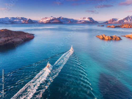 Obraz Aerial view of fishing boats, rocks in the blue sea, snowy mountains and colorful sky with clouds at sunset in winter in Lofoten islands, Norway, Landscape with two motorboats. Top view. Travel - fototapety do salonu