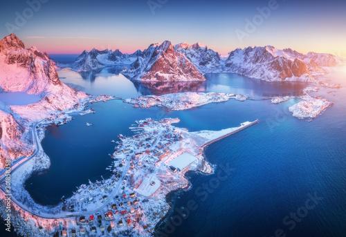 Obraz Widok z lotu ptaka na Reine o wschodzie słońca w zimą. Widok z góry na Lofoty, Norwegia. Krajobraz z błękitnym morzemi zaśnieżonymi - fototapety do salonu