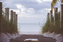 Closeup Shot Of An Open Bible On A Wooden Pathway Towards The Beach With A Blurred Background