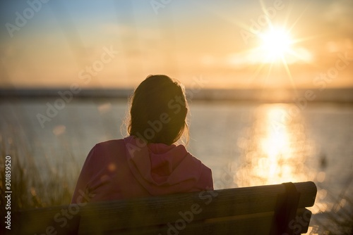 Female sitting on a bench shot from behind with a blurred sea in the background Fotobehang