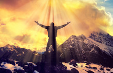 Man Praying With Arms Open On Epic Mountain Top Summit With Light Shining With Arms Out On Top Of Mountain Peak