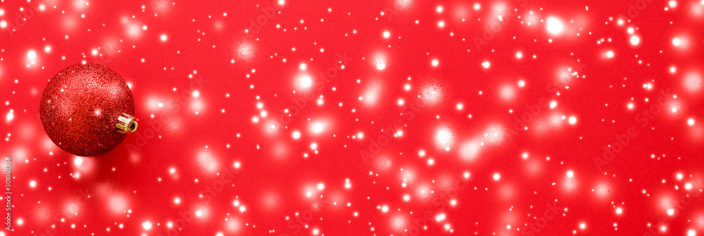 Fototapeta Christmas baubles on red background with snow glitter, luxury winter holiday card