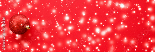 Obraz Christmas baubles on red background with snow glitter, luxury winter holiday card - fototapety do salonu