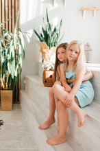 Two Funny And Beautiful Model Girls Hugs And Embrace In Interior Studio With Decorations.
