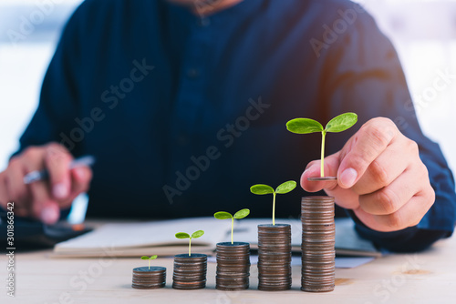 Fotografía businessman stacking coins with plant growing on and use calculator