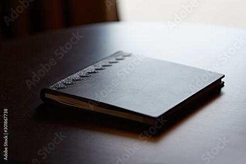 Fényképezés  Note book with hard wooden cover on table by the window in natural light