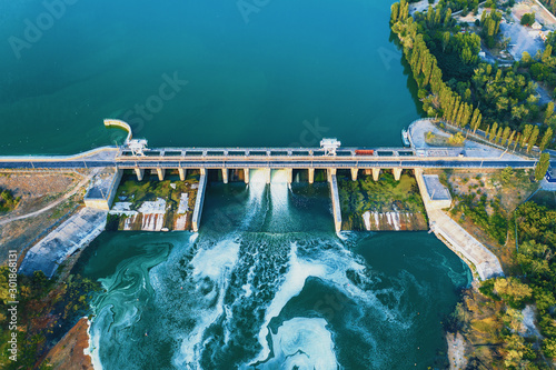 Fototapeta Aerial view of Dam at reservoir with flowing water, hydroelectricity power station, drone photo. obraz