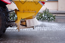 Road Maintenance, Winter Gritter Vehicle. Snow Plow On Pedestrian Street Salting And Cleaning Road. Tractor De-icing Street, Spreading Salt On Footpath. Municipal Service Clears Street During Blizzard