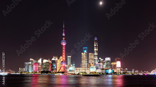Foto auf Leinwand Shanghai Skyline view from Bund waterfront at night with moon on dark blue sky background, Lujiazui is the business quarter of Shanghai, beautiful shanghai night cityscape.