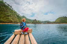 Young Woman Sitting On A Wooden Raft In The Middle Of A Turqeuza Blue Lake Admiring The Landscape Of Wooded Mountains On A Cloudy Day