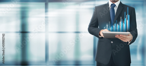 Fototapeta Businessman plan graph growth and increase chart positive indicators in his business,tablet in hand obraz na płótnie