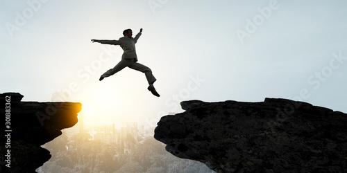 Obraz Businessman jump over leap. Mixed media - fototapety do salonu