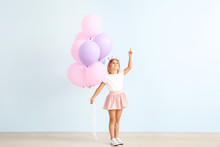 Little Girl With Balloons Pointing At Something Near Color Wall