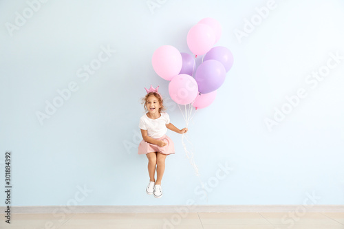 Obraz Jumping little girl with balloons on color background - fototapety do salonu