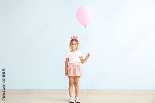 Canvastavla Little girl with balloon near color wall