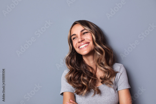 Fototapeta Beautiful smiling woman studio shot on gray background. obraz