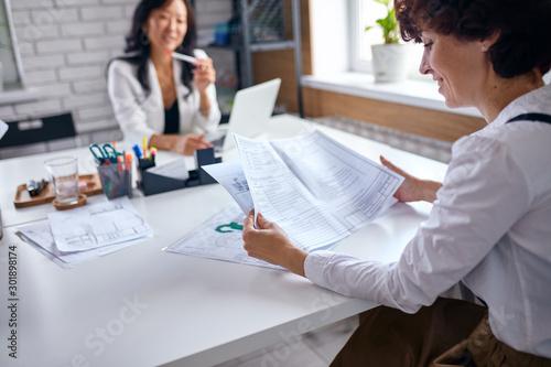 Obraz Beautiful asian director of company listen to caucasian representative holding papers - fototapety do salonu