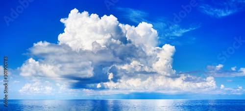 Foto auf AluDibond Dunkelblau White cumulus clouds in blue sky over sea landscape, big cloud above ocean water panorama, horizon, beautiful tropical sunny summer day seascape panoramic view, cloudy weather, cloudscape, copy space