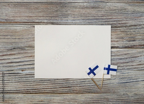 December 6 . Finnish independence day. mini flags on wooden background with white paper sheet