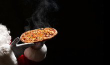 Happy Santa Claus Hold Big Hot Steaming Pizza Offering With Copy Space. New Year And Xmas Fast Food