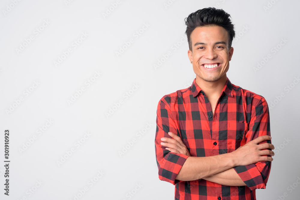 Fototapeta Portrait of happy young Asian hipster man smiling with arms crossed