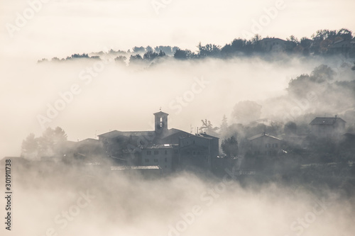 Surreal view of of a little town in Umbria (Italy) almost completely hidden by f Fototapet