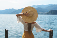 Woman Is Wearing Straw Hat Looking On The Beautiful Lake