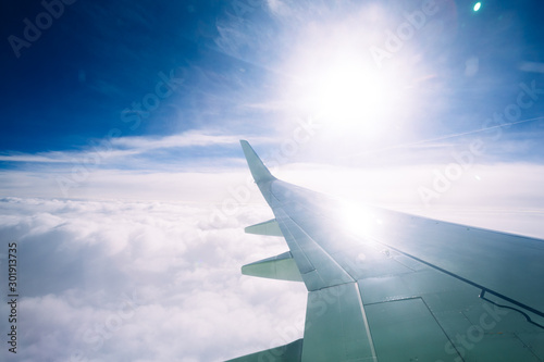 Wing of an airplane flying above the clouds Wallpaper Mural