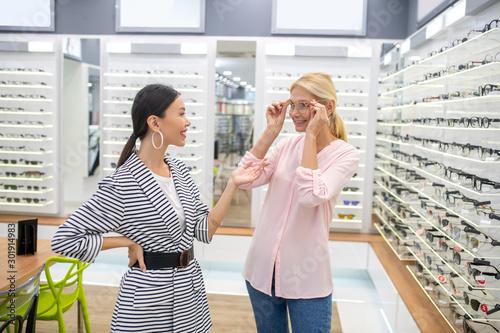 Valokuvatapetti Charming girl wearing stylish earrings helping woman to choose glasses frame