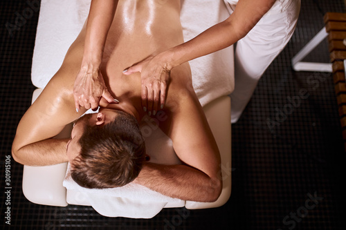 Obraz Young pleasant man having deep tissue massage on white soft towels, lying on black floor, gentle female hands massaging neck of male client, osteopathy treatment - fototapety do salonu