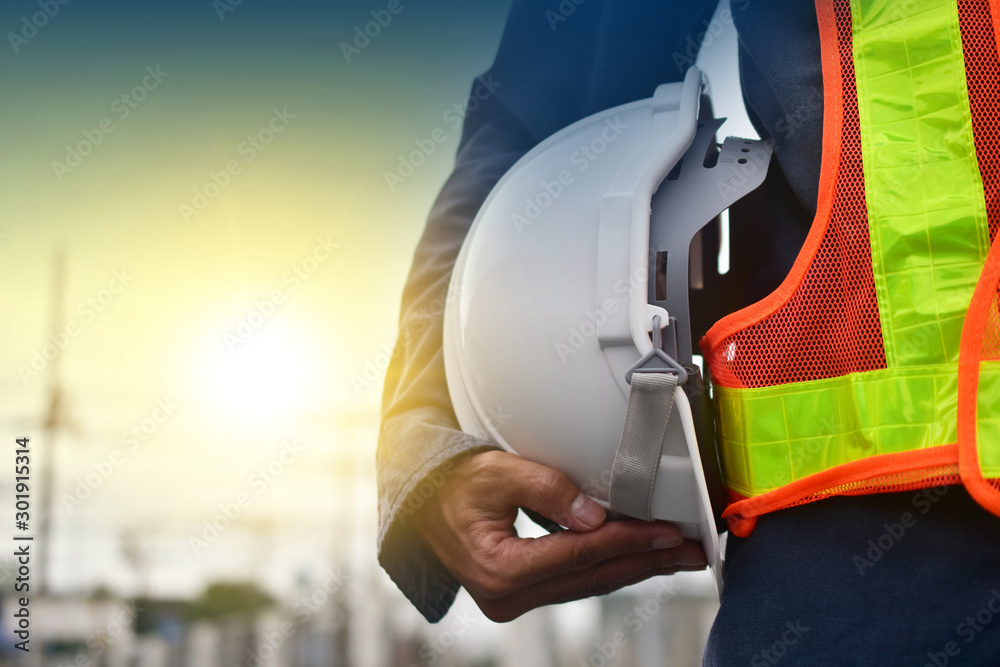 Fototapeta Technician holding white hat safety hard hat sunlight background