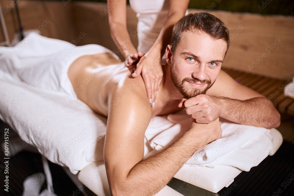 Fototapety, obrazy: Charming handsome man looking at camera with pleasant face, smiling gladly, expressing satisfaction, pleased by good hand massage, resting on soft white towels, demonstrates good mood