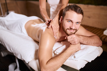 Charming handsome man looking at camera with pleasant face, smiling gladly, expressing satisfaction, pleased by good hand massage, resting on soft white towels, demonstrates good mood