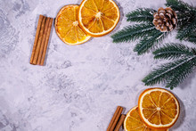 Christmas Or Winter Background. Fir Branches, Cinnamon Sticks And Dried Orange Slices On A Gray Texture. Flat Lay, Top View, Space For Text.