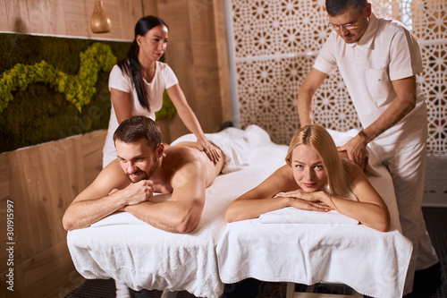 plakat Young charming couple receiving professional relaxation hand massage in wellness beauty spa salon, lying on massage couch, having good time, satisfaction and pleasure concept