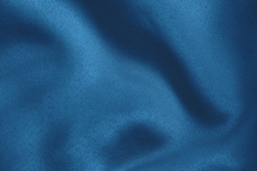 Dark blue colored Background of soft draped fabric. Beautiful satin silk textured cloth for making clothes and curtains. Elegant textile texture. Color trend concept.