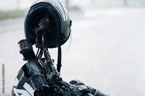 Fototapeta Wet black helmet hanging on handlebar of motorcycle on rainy day
