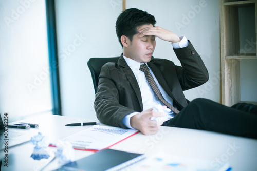 Fototapeta  Serious Asia businessman was stressed in the office room : Overtime and serious