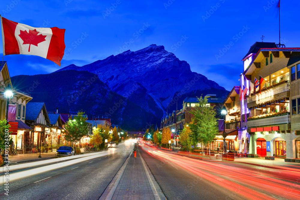 Fototapeta Canadian flag with Banff Avenue at twilight time, Alberta, Canada
